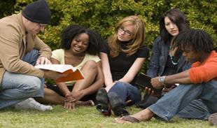 Groupe de jeunes assis dans l'herbe